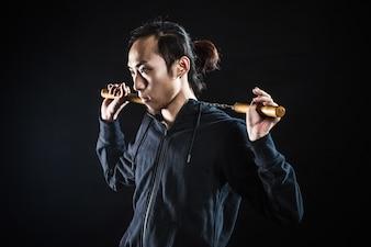 Hombre asiático con nunchakus