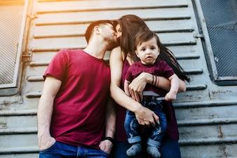 Hombre  besándo a su esposa en la cabeza y esta tiene al bebé