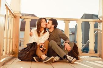 Hombre besando la mejilla de su novia en el porche
