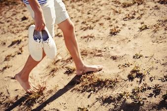 Hombre caminando con los zapatos en la mano en la playa