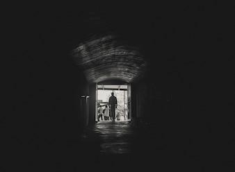Hombre caminando hacia la luz al final de un túnel