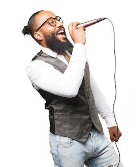 Hombre cantando por un micrófono con la boca abierta