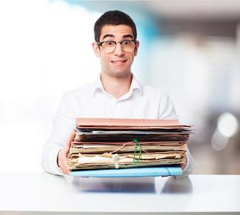 Hombre cargando con un montón de carpetas en una oficina