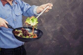 Hombre cocinando verduras