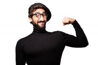 Hombre con boina y gafas de sol apretando los músculos del brazo