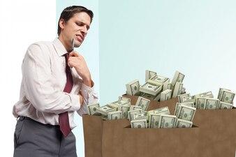 Hombre con cara de asco con bolsas de dinero