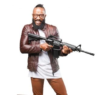 Hombre con cara de loco con una ametralladora