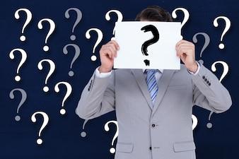 Hombre con cartel con una interrogación y un fondo con interrogaciones