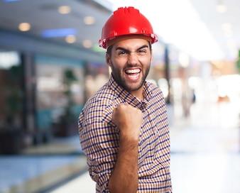 Hombre con casco rojo celebrando con un puño levantado