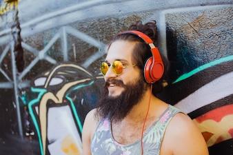 Hombre con gafas de sol escuchando música con auriculares