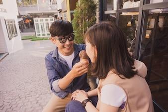 Hombre con gafas de sol ofreciendo un helado a una mujer