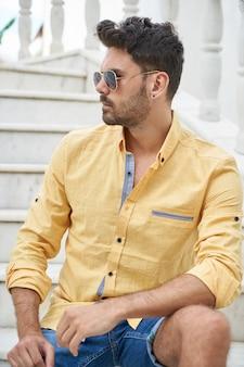 Hombre con gafas de sol y camisa amarilla