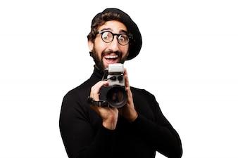Hombre con la boca abierta con una cámara antigua en la mano