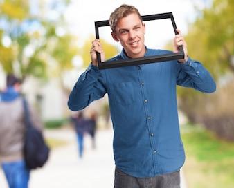 Hombre con la cabeza metida en un marco negro