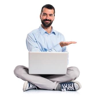 Hombre con la computadora portátil que presenta algo