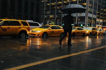 Hombre con paraguas con taxi de fondo