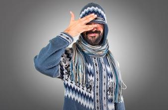 Hombre con ropa de invierno cubriendo sus ojos sobre fondo gris