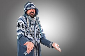 Hombre con ropa de invierno haciendo gesto sin importancia sobre fondo gris