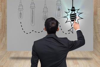 Hombre con traje dibujando bombillas