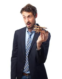Hombre con traje jugando con un avión de madera