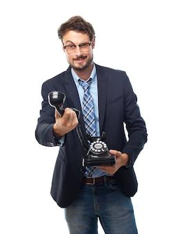 Hombre con traje y gafas de ver con un teléfono en la mano