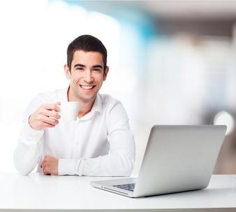 Hombre con un café y un portátil