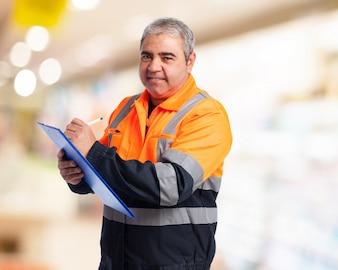 Hombre con un mono de trabajo naranja tomando nota