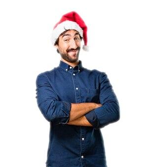 Hombre con un sombrero de papa noel y brazos cruzados