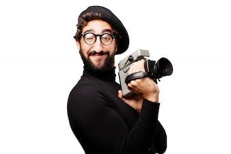 Hombre con una boina y gafas de ver con una videocámara antigua