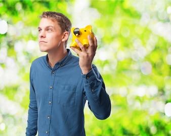 Hombre con una hucha de cerdito amarilla