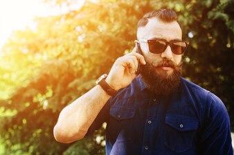 Hombre concentrado hablando por teléfono al atardecer