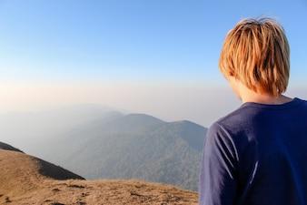 Hombre de espaldas mirando un valle