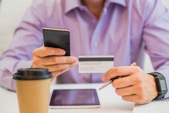 Hombre de la mano la celebración de tarjeta de crédito, disfrutando de compras en línea de internet utilizando tableta de computadora digital en casa.