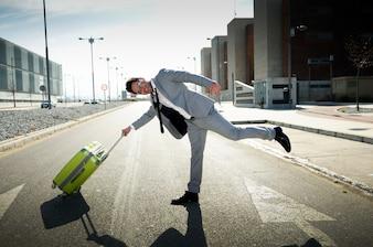 Hombre de negocios alegre jugando con su maleta