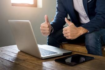 Hombre de negocios asiático joven que muestra el pulgar hacia arriba mientras que se sienta en un café y que trabaja con la computadora portátil.