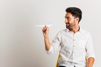 Hombre de negocios con avión de papel en la oficina