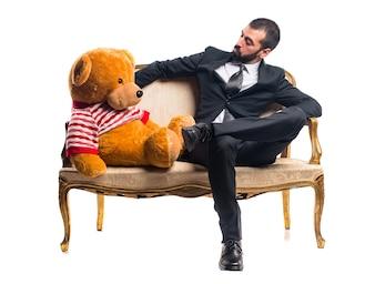 Hombre de negocios con peluche sentado en el sillón vintage