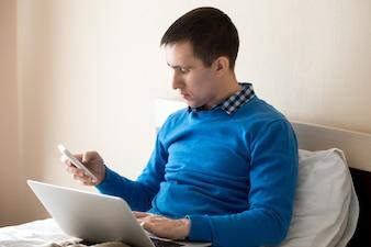 Hombre de negocios concentrado con portátil y móvil