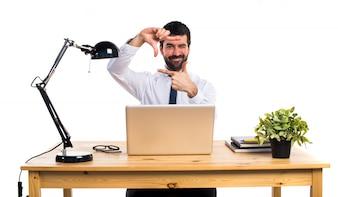 Hombre de negocios en su oficina centrándose con sus dedos
