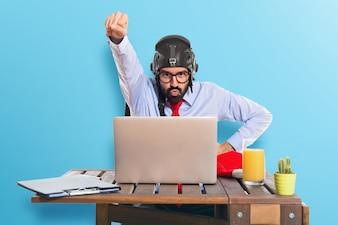 Hombre de negocios en su oficina con el sombrero del piloto en fondo colorido