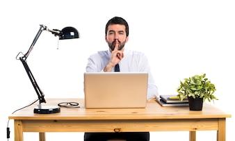 Hombre de negocios en su oficina haciendo gesto de silencio