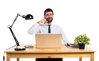 Hombre de negocios en su oficina haciendo gesto de teléfono