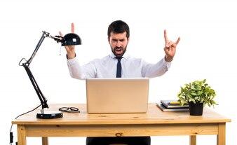Hombre de negocios en su oficina que hace el gesto del cuerno