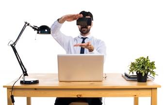 Hombre de negocios en su oficina usando vasos VR sosteniendo algo