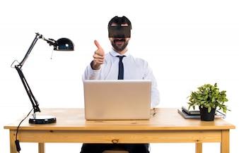 Hombre de negocios en su oficina usando VR gafas con el pulgar hacia arriba