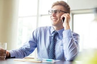 Hombre de negocios feliz que llama en el teléfono en la mesa de la oficina