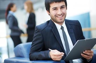 Hombre de negocios feliz sentado con un sujetapapeles