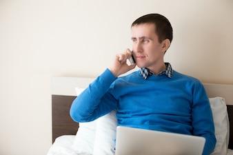 Hombre de negocios hablando por teléfono en la cama