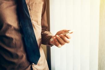 Hombre de negocios joven sosteniendo el teléfono inteligente en la oficina con luz del sol. Filtro tonificado vintage.