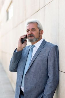 Hombre de negocios mayor con smartphone fuera del edificio de oficinas moderno.